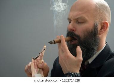A businessman lights a cigar with a lit thousand-ruble bill.