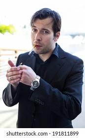 businessman lights up a cigarette