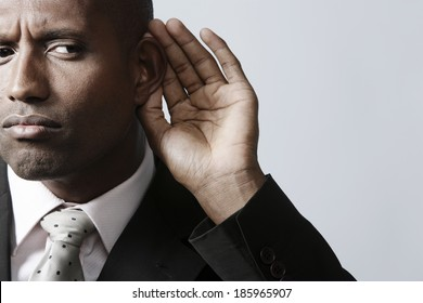 Businessman listening with hand on ear