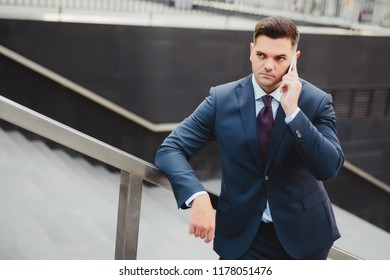 Businessman listens to justifications of partners in imperfect transaction. Young caucasian stands on street and holds phone in hand. Concept of failure.