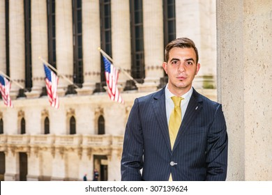 Businessman with little scar on lip - cleft lip, dressing in blue suit, yellow tie, standing outside office. Concept of facing reality, up and down, self assured, self esteem, confidence and success.