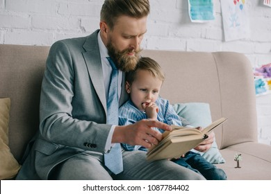 businessman and little son reading book together an sofa at home, work and life balance