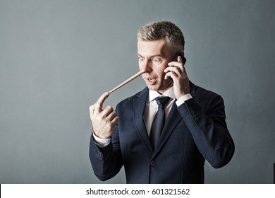 Businessman with long nose on gray wall background. Liar concept.
