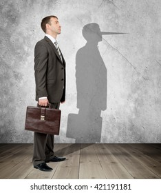 Businessman with long nose on his shadow