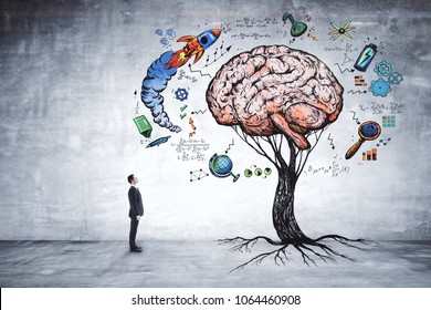 Businessman looking at abstract brain tree in concrete interior. Education, growth, brainstorm and startup concept