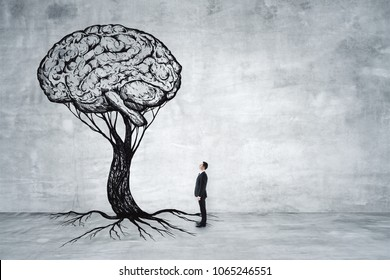 Businessman looking at abstract brain tree in concrete interior. Education, growth, brainstorm and success concept