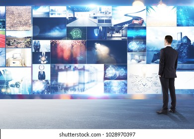 Businessman looking at abstract digital picture gallery. Multimedia and search concept