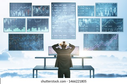 Businessman looking at abstract financial interface on bright sky with clouds background. Finance and invest concept