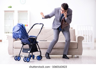 Businessman looking after newborn baby at home and teleworking