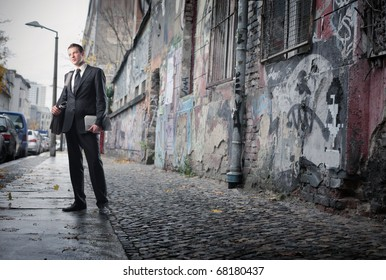 A businessman is looking around in a poor neighborhood