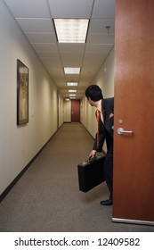 Businessman looking around suspiciously with his briefcase in hand in an empty hallway