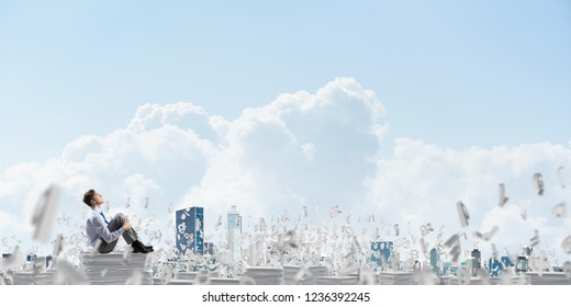 Businessman looking away while sitting on pile of documents among flying letters with cloudly sky on background. Mixed media.