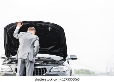 Businessman looking at breakdown car against sky