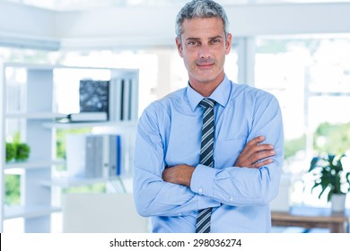 Businessman looking at camera with arms crossed in office