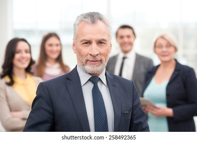 Businessman looking at camera. His team standing behind. Office interior with big window