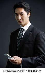 Businessman, looking at camera, holding mobile phone