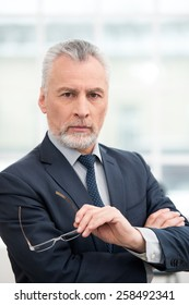 Businessman looking at camera. Office interior with big window