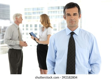 Businessman looking at camera on foreground and business people talking in the background