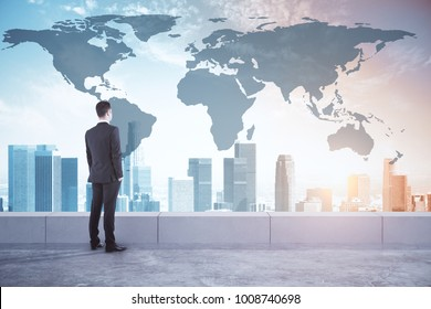 Businessman looking at city with abstract map. International business and research concept. Double exposure