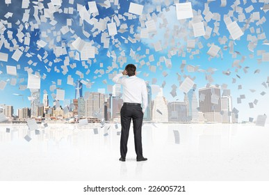 Businessman is looking at the city while papers are falling from the sky.