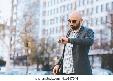 Businessman looking at the clock on street