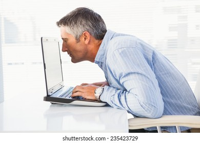 Businessman looking closely at the laptop in his office