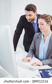Businessman looking in computer monitor while female colleague typing at desk in office