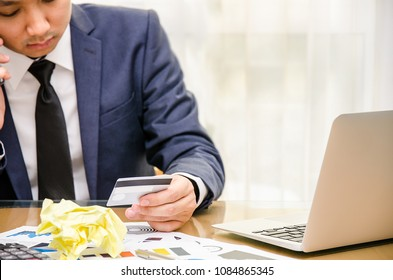 Businessman looking at credit card in stress. Calculator accounting costs, charges, taxes and mortgage for paying bills looking worried and stressed