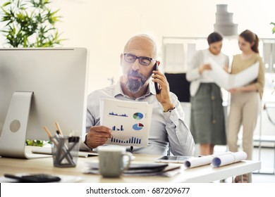 Businessman looking at document while talking on phone