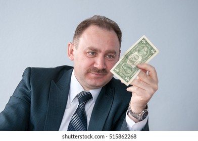 Businessman looking at a dollar in his hand