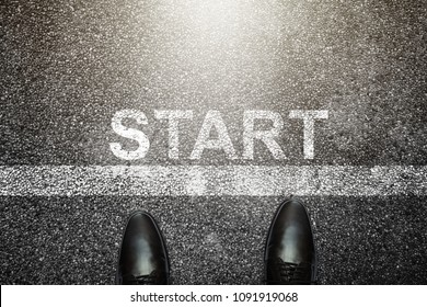 Businessman is looking down at his feet on a Asphalt road with start letters painted on the surface. An image of a milestone roadmap is a representation of success in the future goal