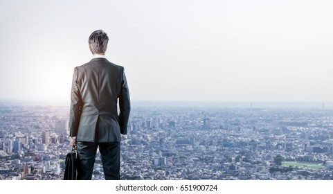 businessman looking down a modern city. business prospect concept.