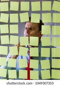 Businessman looking at a glass with some post it