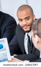 Businessman looking graphics of business plan. Four smiling successful businessmen sitting at table in office while discussing their business doings. Young people talking in office