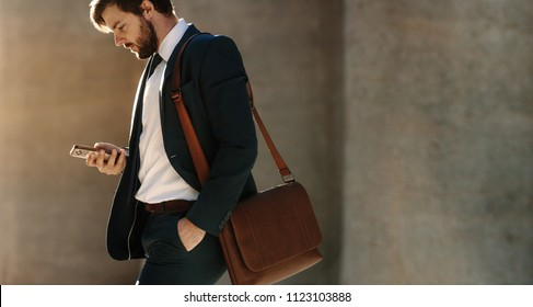 Businessman looking at his mobile phone while walking on street to office. Busy office going man commuting to office carrying his office bag and using mobile phone.