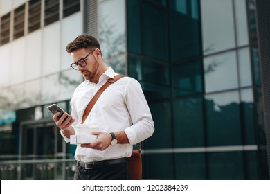 Businessman looking at his mobile phone standing outside a glass façade building. Man holding two coffee cups in hand using mobile phone standing outdoors.