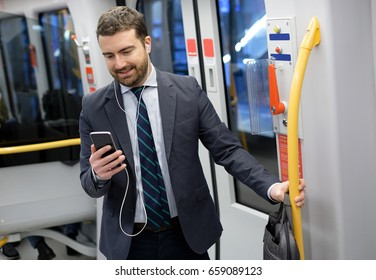 Businessman is looking at his mobile phone while is going to work
