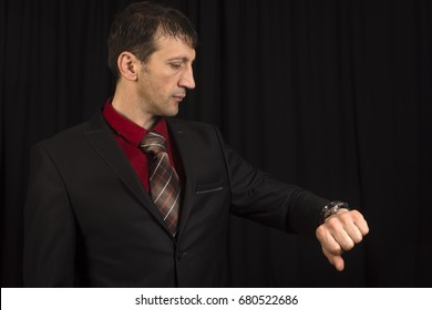 The businessman is looking at his wrist watch and waiting on black background.