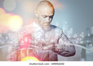 Businessman looking at his wristwatch double exposure