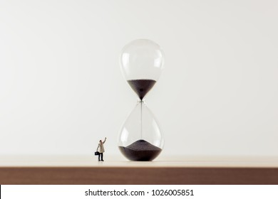 Businessman looking at hourglass. Macro photo.