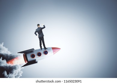 Businessman looking into the distance on abstract launching rocket on gray background. Startup and new business concept.