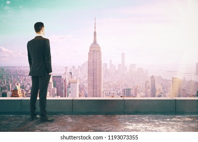 Businessman looking into the distance on concrete rooftop with New York city view and sunlight. Research and think concept