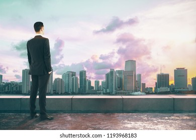 Businessman looking into the distance on concrete rooftop with city view and sunlight. Research and work concept