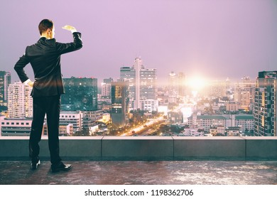 Businessman looking into the distance on concrete rooftop with city view and sunlight. Research and tomorrow concept
