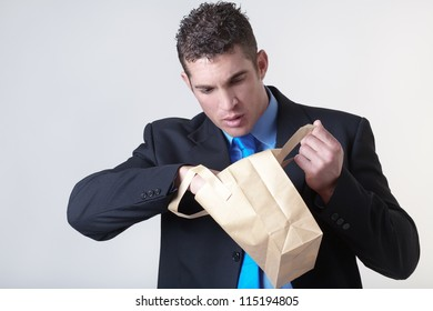 businessman looking into a paper bag to see what he can find