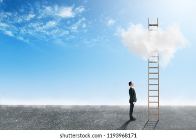 Businessman looking at ladder on bright blue sky background with clouds. Paradise and opportunity concept