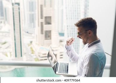 Businessman looking at laptop holding his fist up. He is on the top floor.