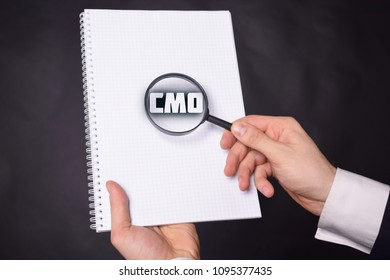 Businessman looking at a magnifying glass word:CMO