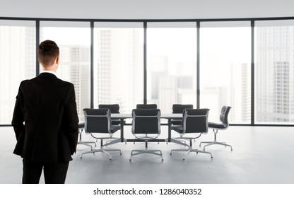 Businessman looking megalopolis through window. Contemporary white office