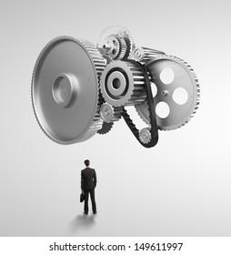 businessman looking at metal gears and cogwheels